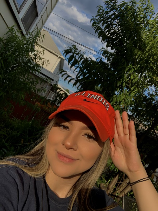 Student poses for photo on campus in orange hat
