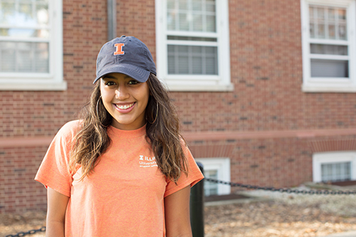 Student poses for photo in blue and orange Illinois hat
