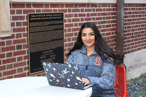 Nidhi Shastri poses while on her computer in front of a brick wall