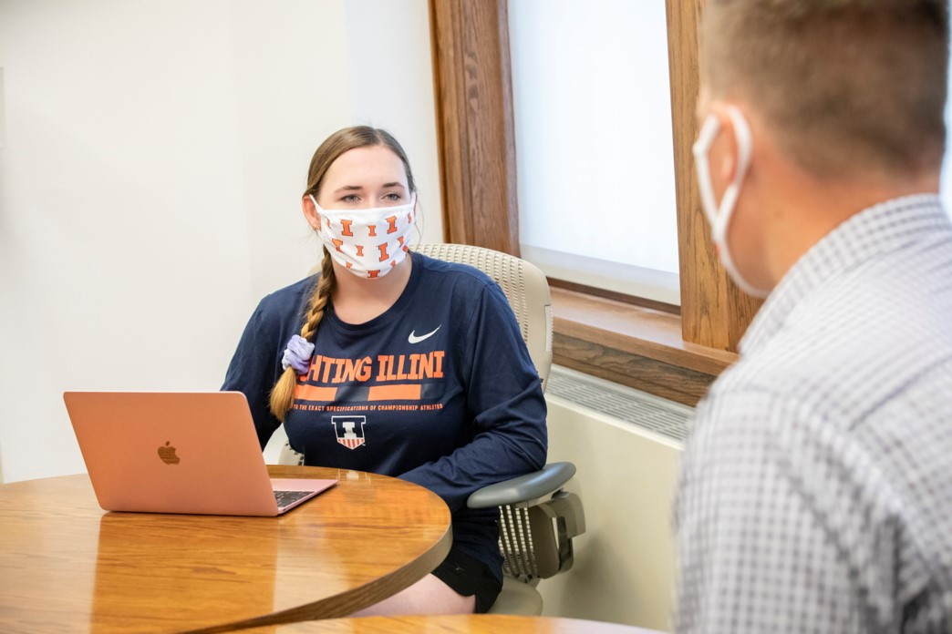 Student sits at table with a mask on.