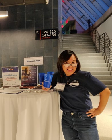 LAS junior Cherish Recera poses for a photo in front of a Research Park promotional table at the State Farm Center.