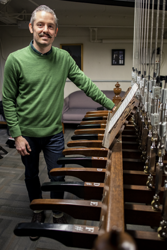 Jonathon Smith poses next to chimes console