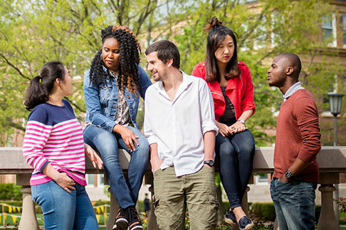 A group of students talk on the Quad