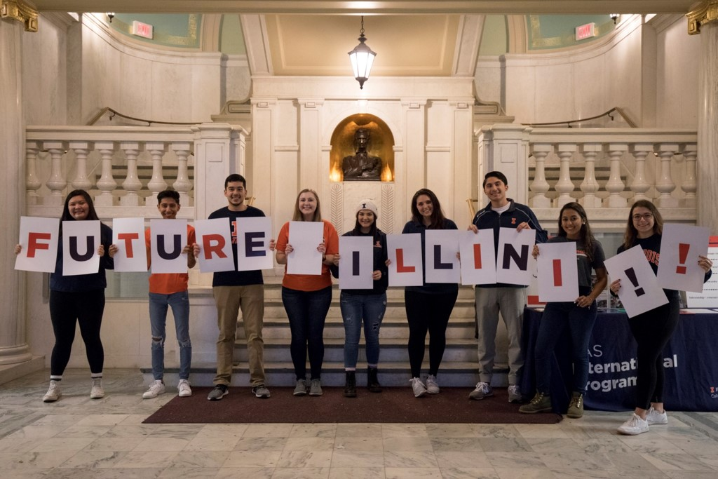 "Students hold up cards to say ""Future Illini!!"""