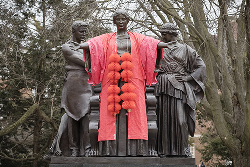 The Alma Mater statue dressed in a red robe with Chinese lanterns draped around her neck