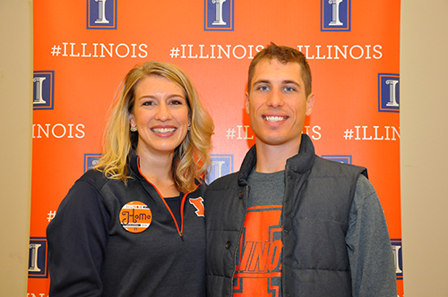 Two alumni wearing orange and blue pose in front of an Illini backdrop