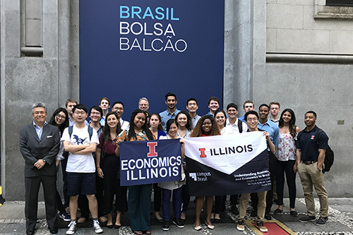 Students and faculty members pose with Illini and Illinois Economics flags in Brazil.