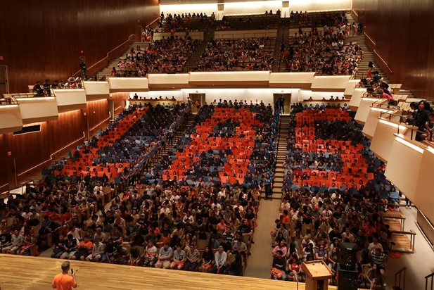 Nearly 1000 students hold up cards at freshmen orientation to spell LAS.