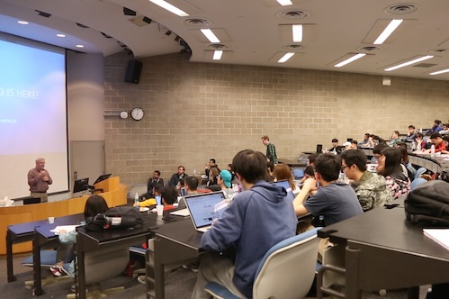 Students participate in a datathon by sitting in a large lecture-style classroom.