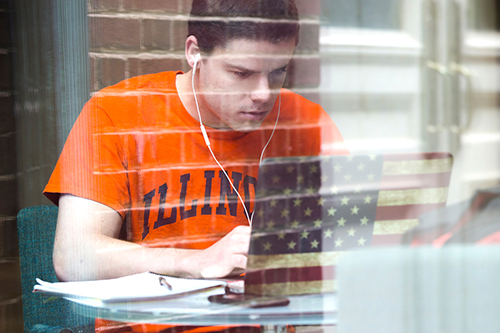 A student wearing an Illinois shirt works on a laptop with a cover showing an American flag.