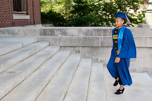 A student in a cap and gown walks up the stairs to Foellinger Auditorium