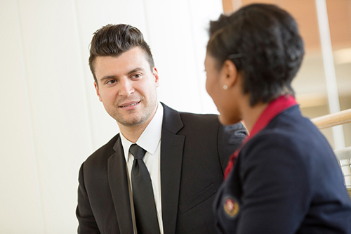 A man in a sut talks to a woman in a suit
