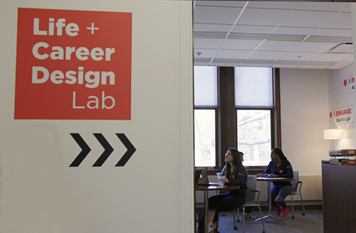 A peek inside the doorway of the Life + Career Design Lab. Two lab interns are talking to students.