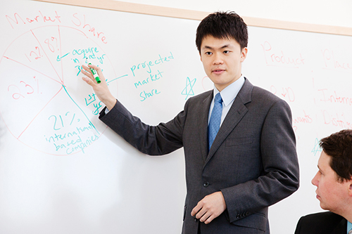 A student in a suit makes a presentation on a white board