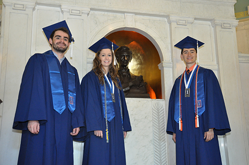Three graduating scholars wearing caps and gowns stand next to the bust of Abraham Lincoln in the lobby of Lincoln Hall.