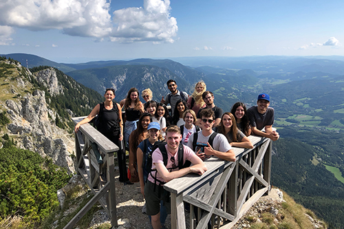 A group of students studying abroad in Vienna post on a mountain