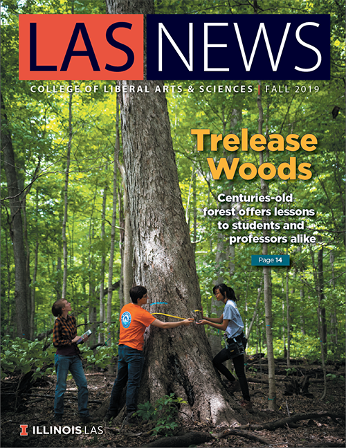 "The cover of the fall 2019 edition of LAS News, which bears the headline, ""Trelease Woods: Centuries-old forest offers lessons to students and professors alike."" A photo of three students surveying a tree in the woods is the image."