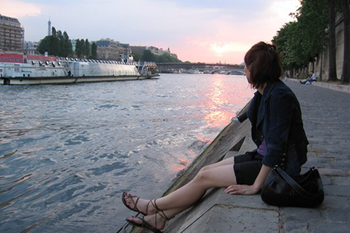 A young woman observes the sunset by a waterway in Paris