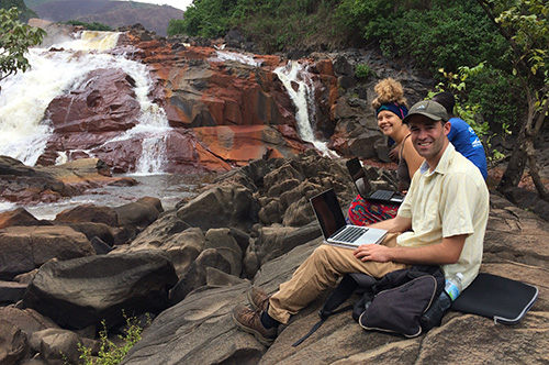 Students with laptops pose near a waterfall in Sierra Leone