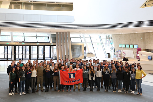 A group of students pose with an Illinois flag