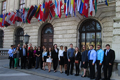 Students pose in front of flags outside the Vienna International Center