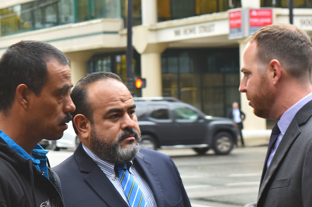 Matt Eisenbrandt, right, speaks to a Guatemalan client and his lawyer in Vancouver prior to a court hearing concerning a Canadian mining company. (Image courtesy of Matt Eisenbrandt.)