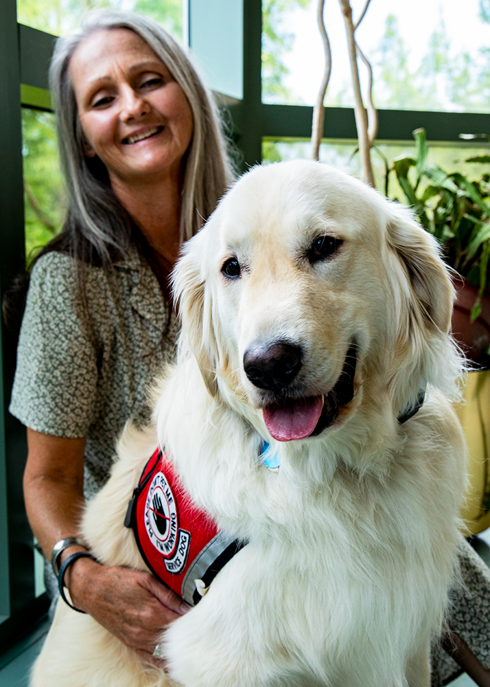 Joey Ramp, a senior in molecular and cellular biology, relies upon the support of her service dog, Sampson, to conduct research in a laboratory. (Photo by Jesse Wallace.)