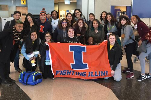 LAS students pose with an Illini flag at the airport before departing on a study abroad trip