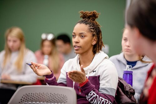 A student gestures as she makes a point in class