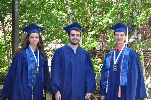 Three Lincoln Scholars in graduation regalia pose in the courtyard of Lincoln Hall