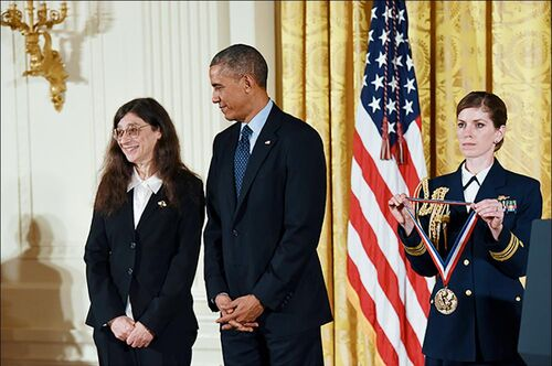 Former President Barack Obama looks at May Berenbaum as a woman in a military uniform holds the National Medal of Science