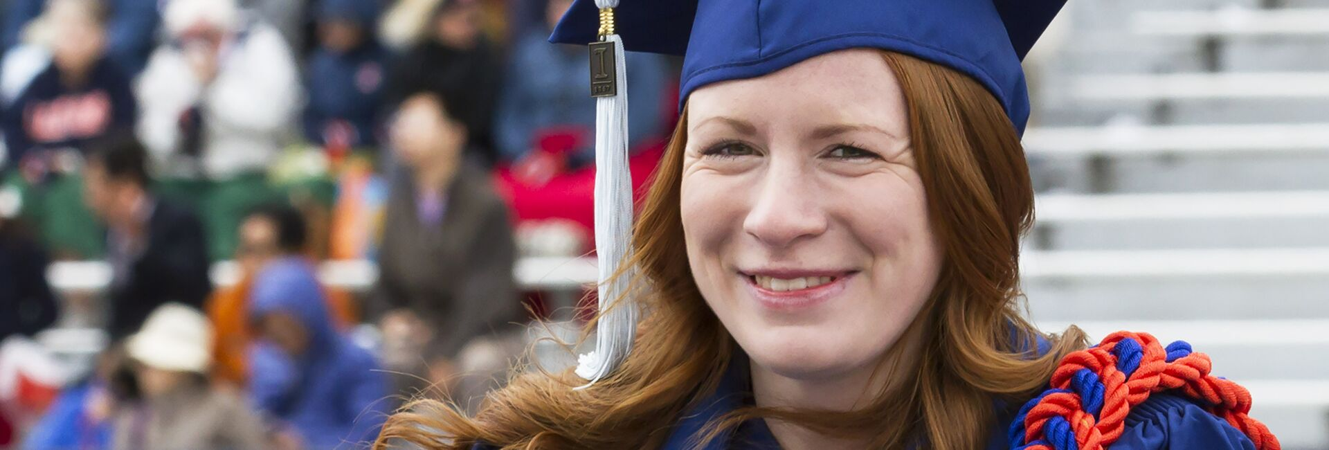 A student wearing a cap and gown smiles