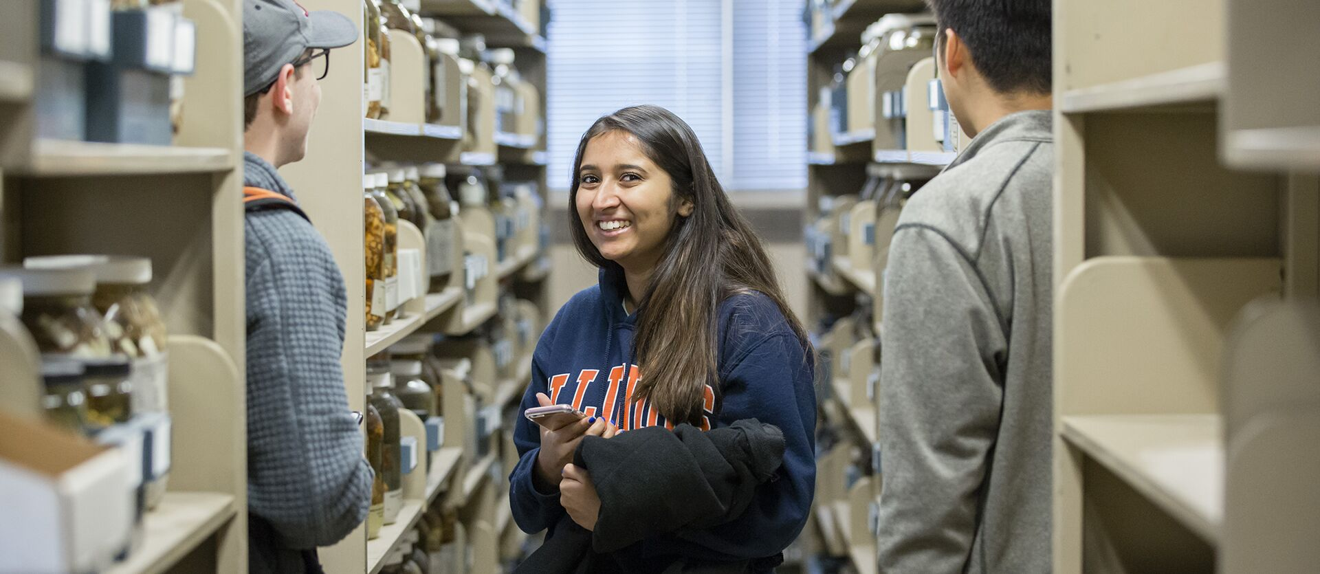 A student smiles as she stands amid shelves with jars of snake specimens