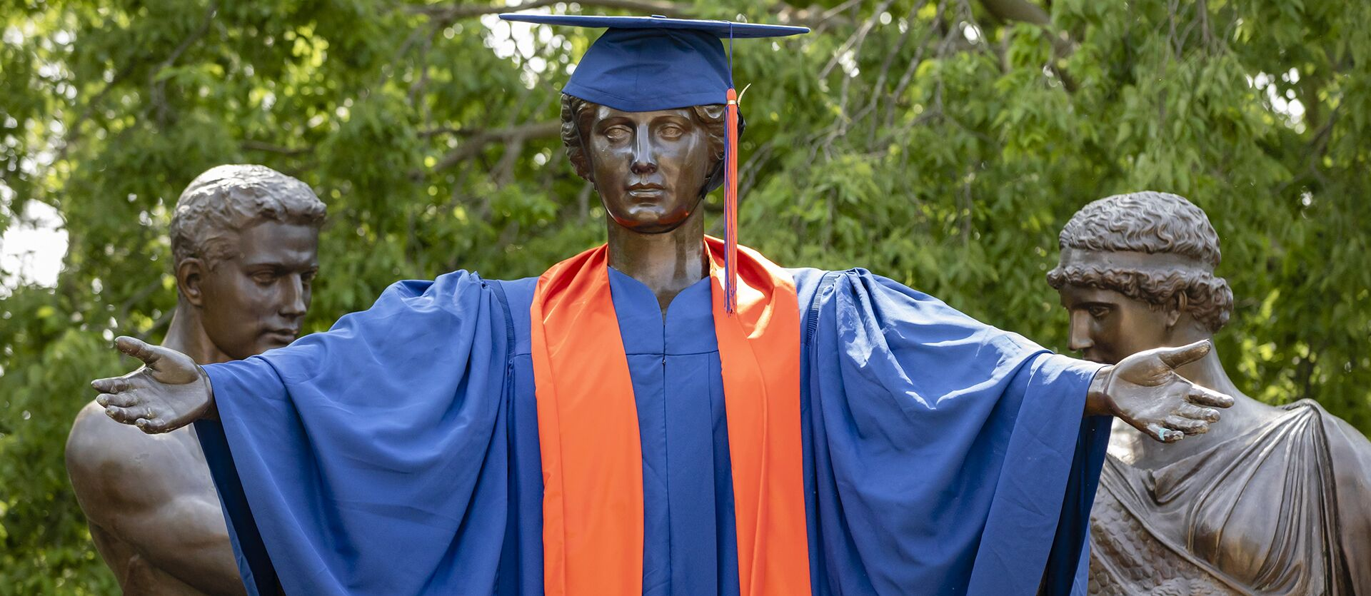 The Alma Mater statue, dressed in a blue and orange cap and gown