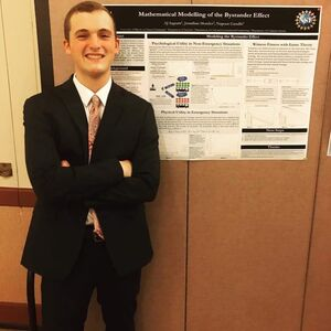 AJ Ingram poses in front of undergraduate research poster