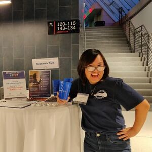 LAS junior Cherish Recera poses for a photo in front of a Research Park promotional table at the State Farm Center